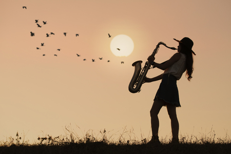 Woman play saxophone with sunset or sunrise background