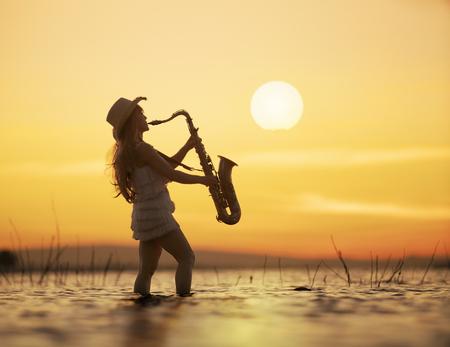 Femme jouant du saxophone sur l'eau avec fond sunsey Banque d'images