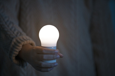 Women hand holding light bulb, concept of save earth