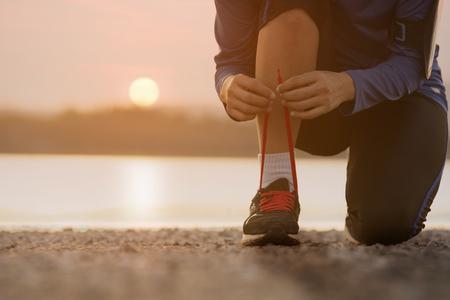 Close up woman tying shoe laces,sport concept