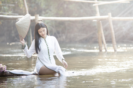 woman with Vietnam culture traditional dress, Ao dai  in the river