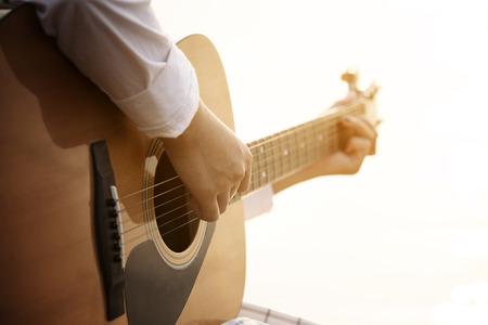 Close up hand playing guitar