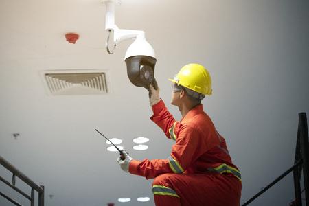 Technician fixing video surveillance camera or CCTV.