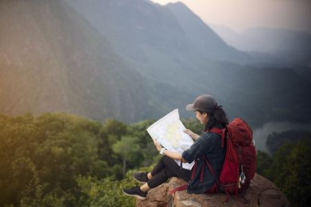 Backpacker woman sitting on top of mountain and looking map with nature background Stock fotó