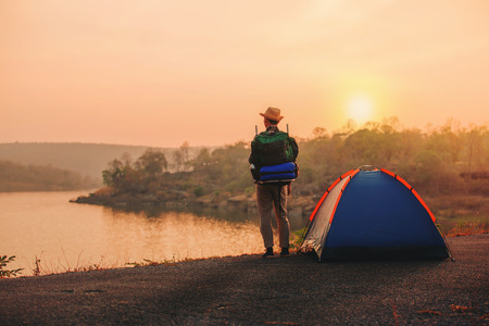man backpack with camping tent in camping site beside the lake with sunsey or sunrise background Stockfoto