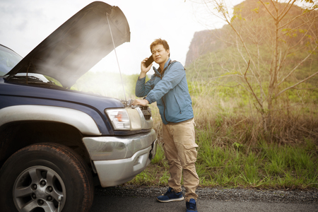 Man with broken car on the country road using mobile phone