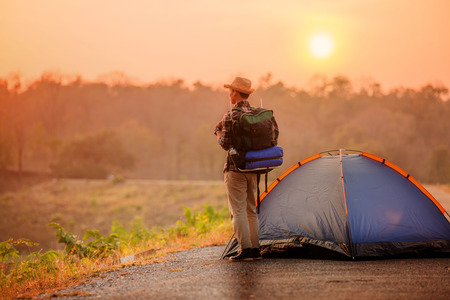 man backpack with tent in camping site with sunsetor sunrise background Stockfoto