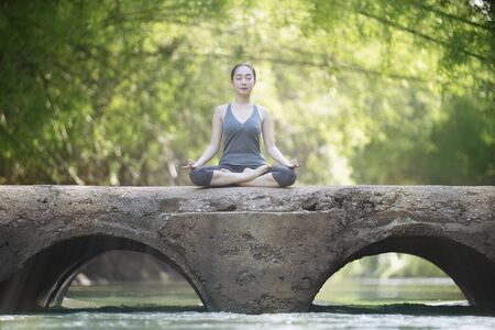 Woman practice yoga on old bridge with nature background