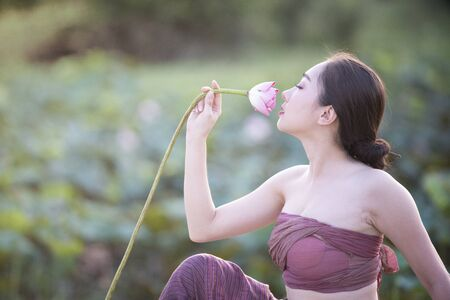 Woman holding lotus with traditional dressing Stockfoto - 125008802