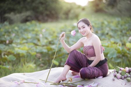 Woman holding lotus with traditional dressing