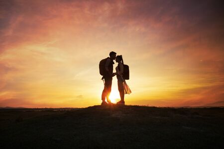 Silhouette romantic couple with sunset or sunrise background