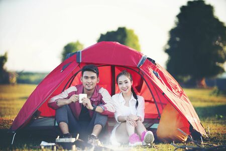 Romantic couple sitting in tent at camping site