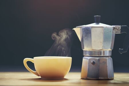 Cup of coffee with coffee maker on black background Stockfoto