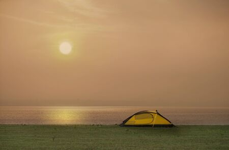 Tent in camping site beside the sea with sunset or sunrise background Stockfoto - 126578278