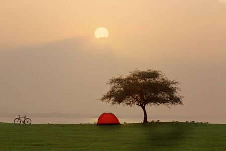 Tent in camping site beside the sea with sunset or sunrise background Stockfoto - 126578296