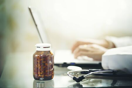 Doctor using laptop with bottle of medical drug,focus at foreground