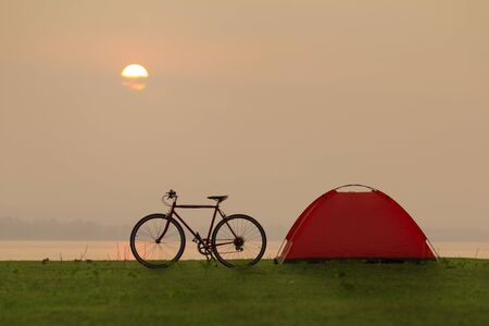 Tent and bicycle in camping site with sunset or sunrise background