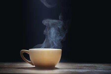 Taza de café con vapor sobre fondo negro