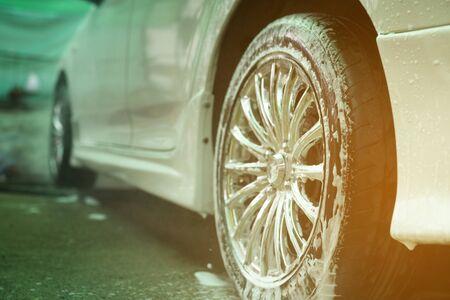 Washing white car with foam