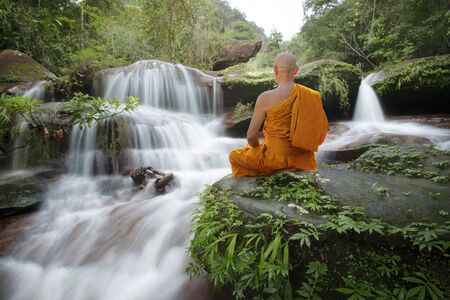 Buddha monk practice meditation at beautiful waterfall Stockfoto - 129176160