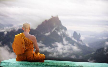 Le moine de Bouddha pratique la méditation devant la montagne Banque d'images