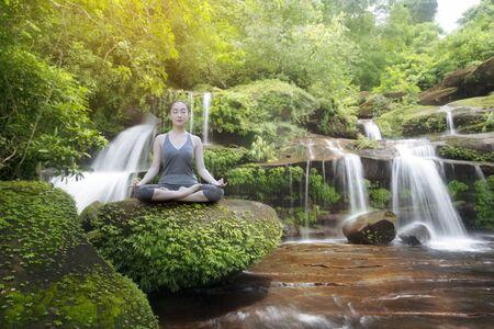 Woman practice yoga with beautiful waterfall