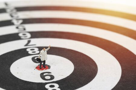 Miniature people businessman standing on center point of dart board