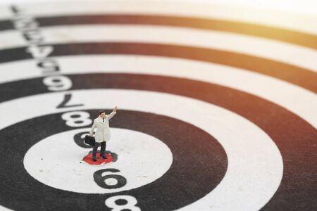 Miniature people businessman standing on center point of dart board Stockfoto - 129429884