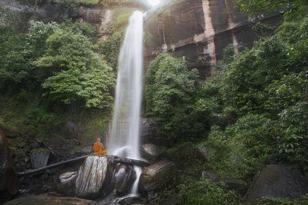 Buddha monk practice meditation at beautiful waterfall