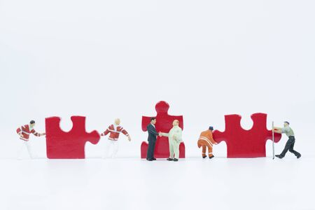 Miniature people hand shaking in front of assembly jigsaw puzzle ,business partner concept.