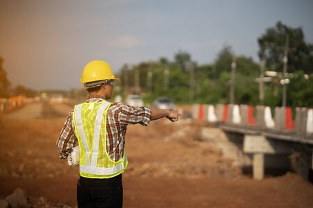 Engineer holding blueprint in construction site
