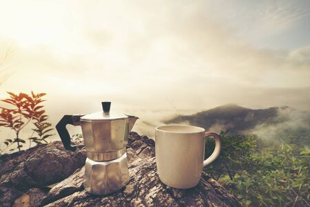 Coffee cup ,moka pot, with mountain and fog background