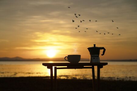 hot coffee with moka pot beside the lake with sunrise background