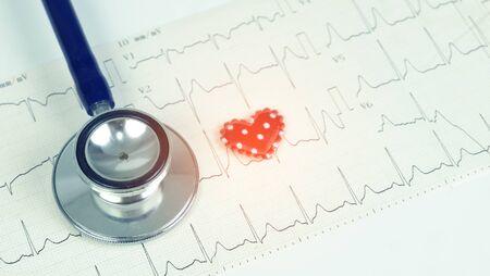 Estetoscopio y forma de corazón rojo en el electrocardiograma, concepto de atención médica
