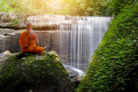 Buddha monk practice meditation with waterfall Banque d'images