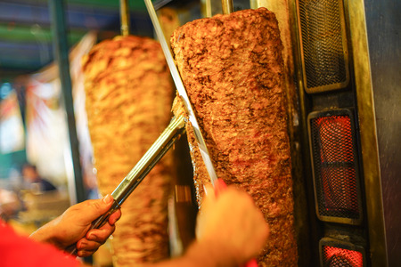 Chef's arm moving to cut a doner kebab meat