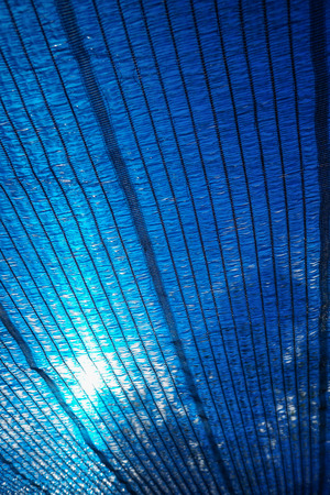 to shading: Sun Through a blue Shading net, plastic awning used as a sunshade.