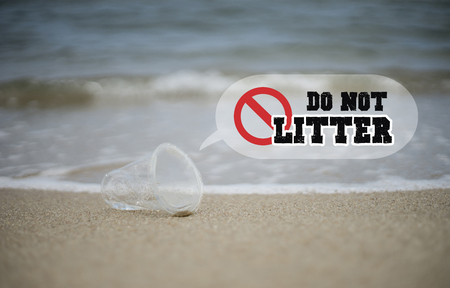 pollute: plastic glass on the beach, Photo of Dont pollute, text do not litter