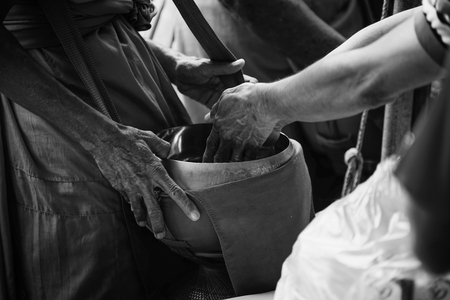limosna: two hand of thai people Buddhism give alms to monk in alms bowl, black and white high contrast picture style,selective focus