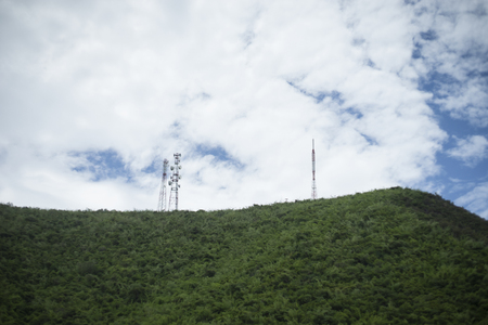 stanchion of Telecommunication mast TV antennas wireless technology on a hilltop of green mountain, blue sky and cloud in background,filtered image,selective focus