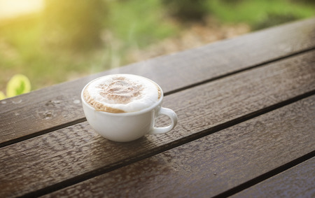 decaffeinated: hot coffee in the morning on wood table with blurred garden in background,selective focus,filtered image,light effect added