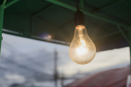 out door: close up lights bulb hanging on a bar with flare of light bulb ,out door,filtered image,selective focus