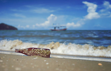 rudeness: sea acorn colony on a brown glass bottle dumped pollute at the sand beach,blurred splash of sea wave and blue sky in background,filtered image,selective focus Stock Photo