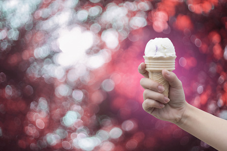 gelati: a woman hand holding Ice cream cone with abstract bokeh background,filtered image,colorful picture style Stock Photo