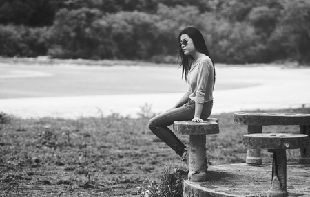young asian woman wearing a sunglass sitting on marble chair near the beach,black and white,sad concept,selective focus Stock Photo