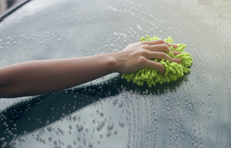 muck: close up woman hand hold a brush washing over the Windshield of the car,woman can wash,woman can do