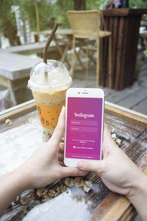 linked hands: prachuapkhirikhan,thaialnd-august 6,2016: woman hand holding Apple iPhone with Instagram application on the screen,at coffee cafe,Instagram is a photo-sharing app for smartphones Editorial