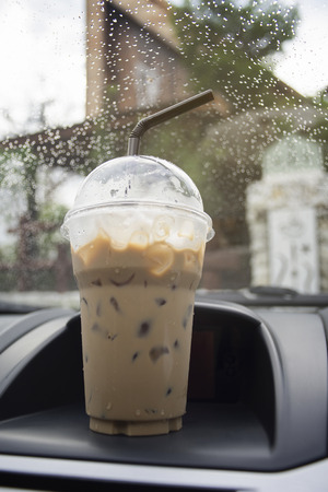 put away: transportation and vehicle concept - take away cup of iced coffee put on a front console of a car with water drop of raining,boost the energy to drive