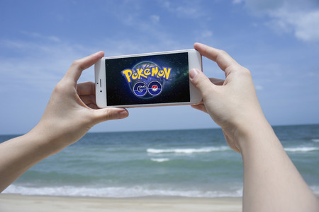 play popular: Prachuapkhirikhan,Thailand - August 6,2016 : woman hand holding smart phone to play Pokemon Go,popular virtual reality game for mobile devices,blurred sea in background,first day opened in thailand