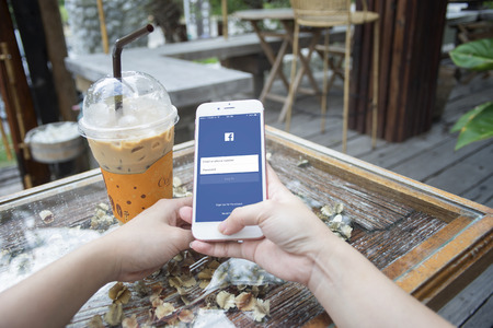 mark zuckerberg: prachuapkhirikhan,thaialnd-august 6,2016: woman hand holding a smartphone with Facebook page on screen,at coffee cafe,Facebook is very well know social networking service founded in 2004 by Mark Zuckerberg